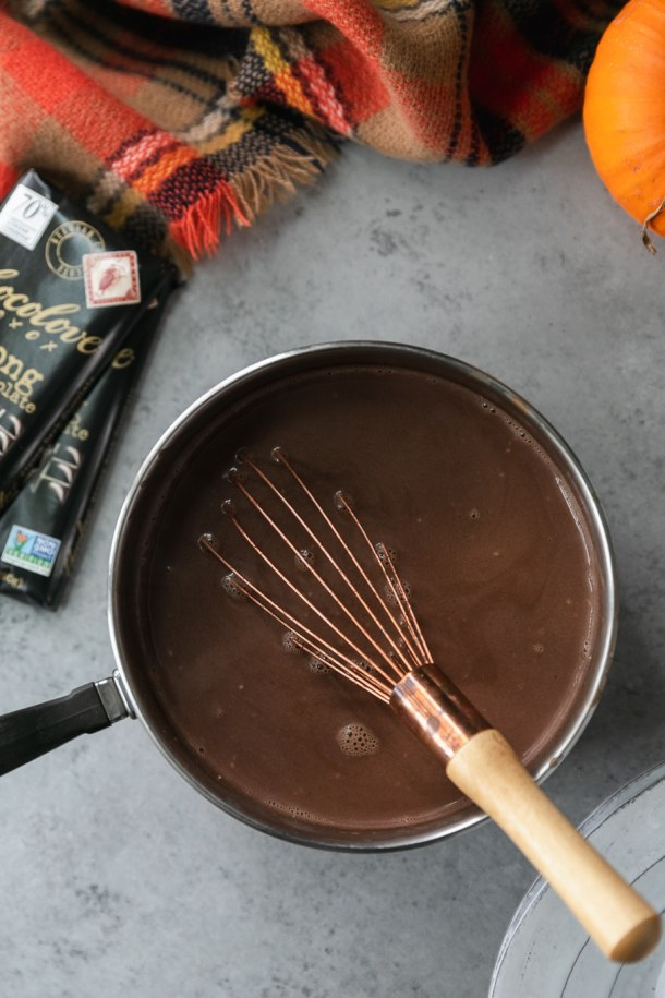 Overhead shot of a saucepan filled with hot chocolate and a bronze whisk with a wooden handle, with two black chocolate bars off to the side and a plaid scarf