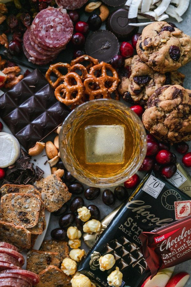 Overhead close up shot of a chocolate and bourbon cheeseboard with apples, cranberries, crackers, pretzels, caramel corn, assorted cheeses, salami, and candy