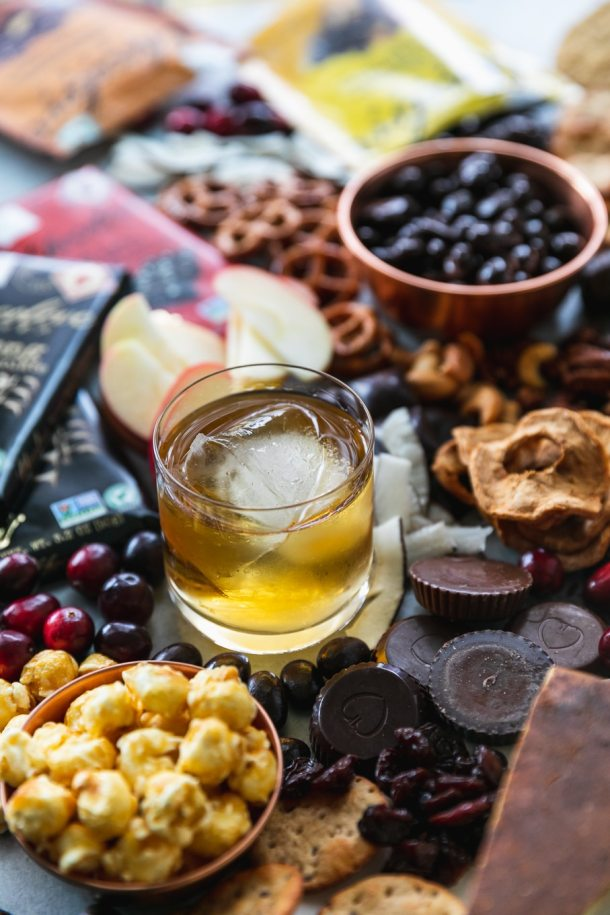 Close up shot of a glass of bourbon surrounded by cheeses,dried fruit, chocolate, pretzels, and caramel corn
