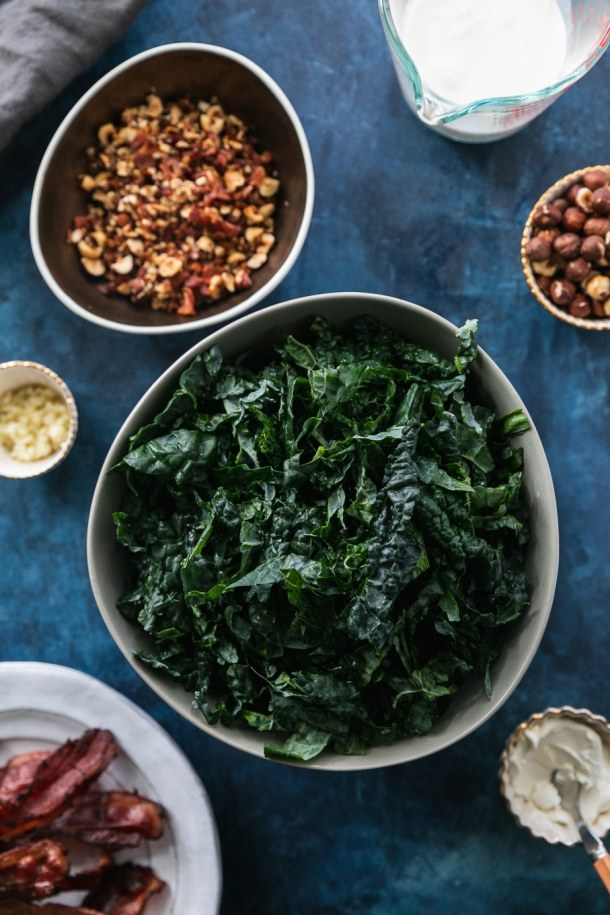 Overhead shot of a bowl of shredded kale, a bowl of chopped hazelnuts, a plate of bacon, a ramekin of garlic, and a ramekin of cream cheese on a dark blue background