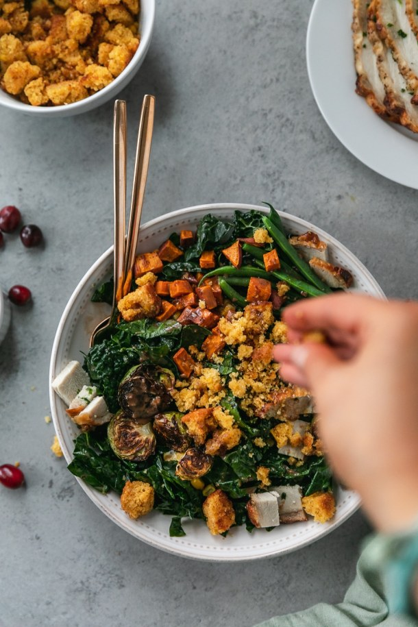 Overhead shot of a thanksgiving leftovers kale salad being sprinkled with cornbread croutons
