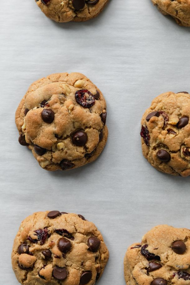 Overhead close up shot of dark chocolate chip cranberry walnut cookies on a baking sheet