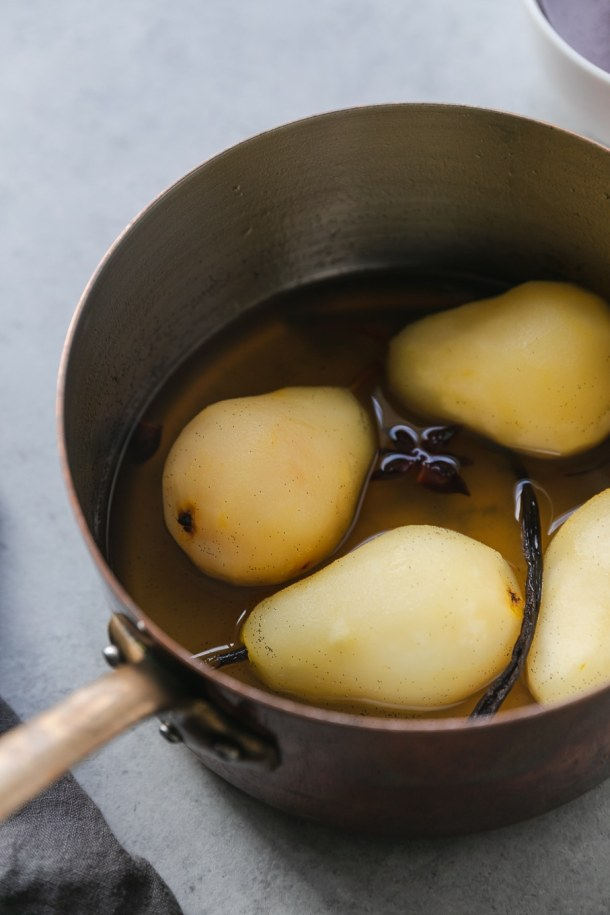 Close up shot of a copper saucepan with 4 poached pears in it with a vanilla bean and a star anise pod floating in it