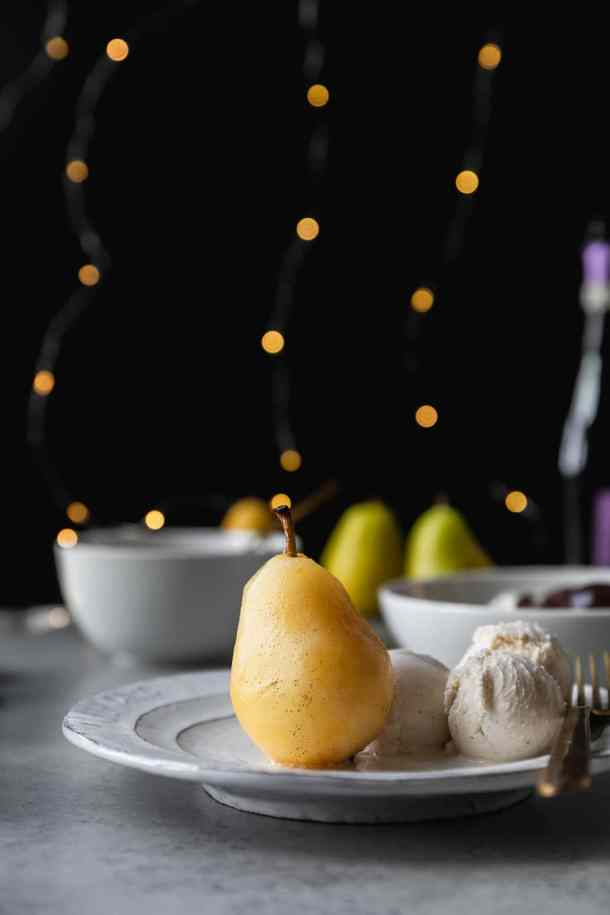 Forward facing shot of a poached pear with ice cream on the side on a white plate with a black background and twinkle lights behind it
