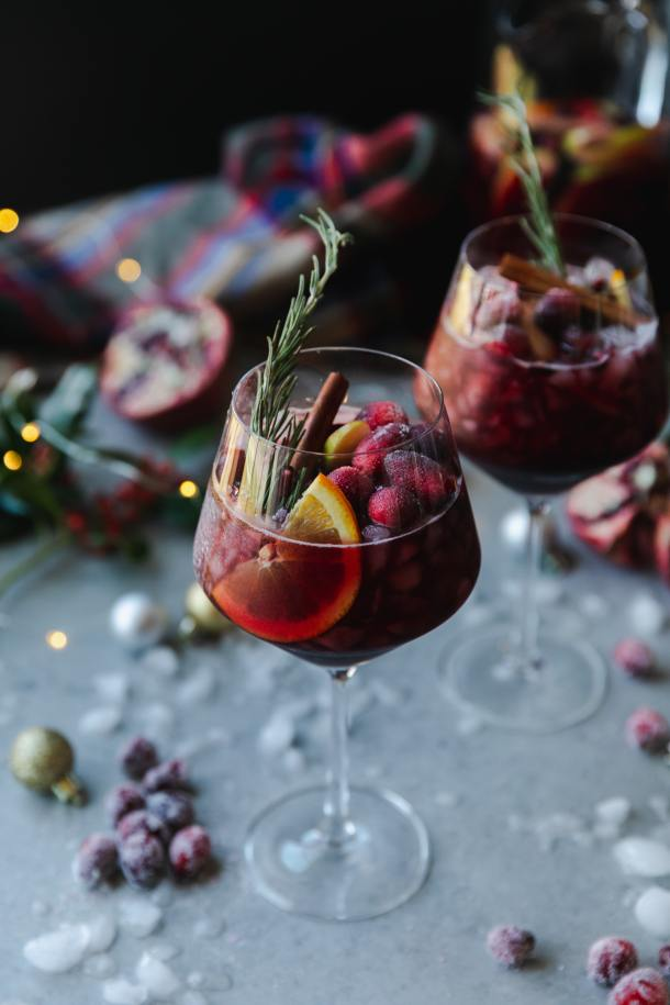 Close up shot of a wine glass filled with red sangria, an orange slice, sugared cranberries, a cinnamon stick, and a rosemary sprig with another glass behind it