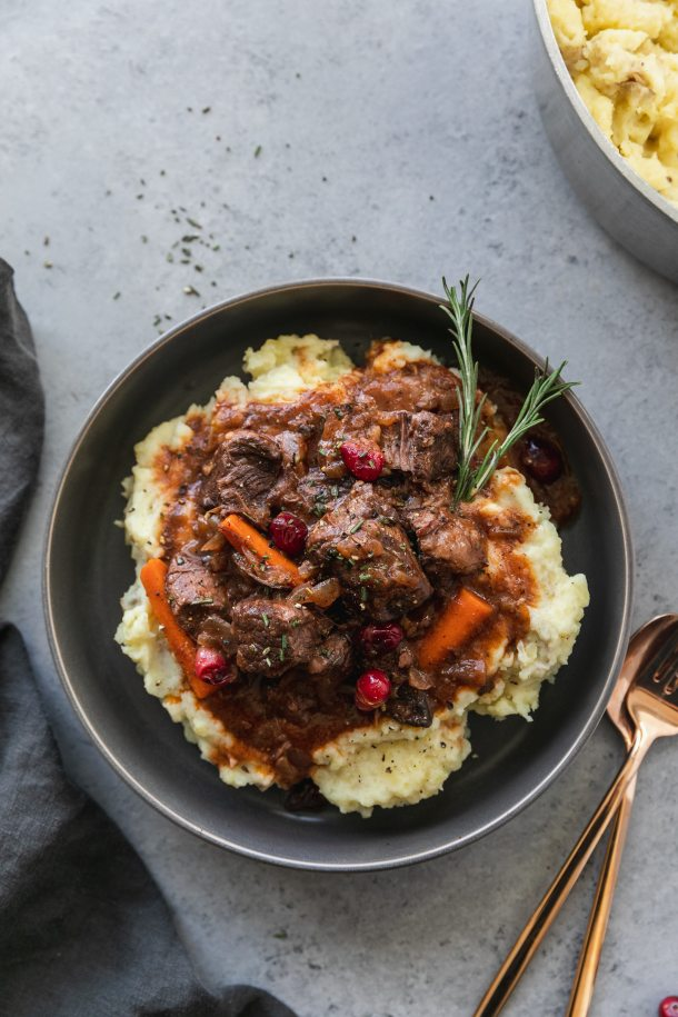 Overhead shot of a bowl of mashed potatoes topped with beef stew and a rosemary sprig with a gold fork and spoon next to the bowl