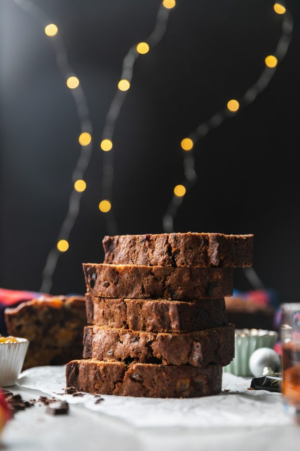 Forward facing shot of a stack of fruitcake slices with twinkle lights against a black background