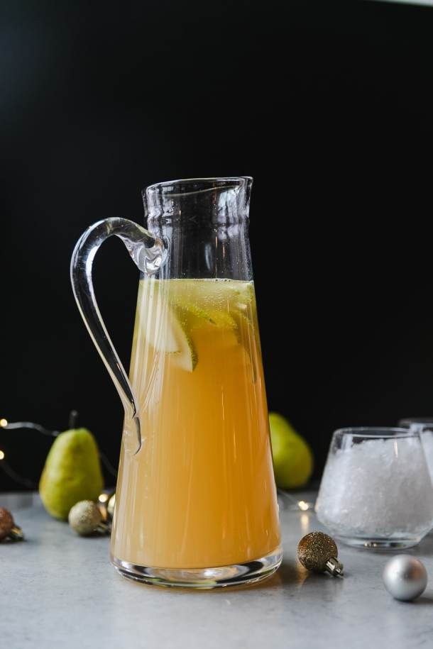 Forward facing shot of a pitcher filled with pear ginger champagne punch with a glass of crushed ice beside it and green pears in the background against a black background