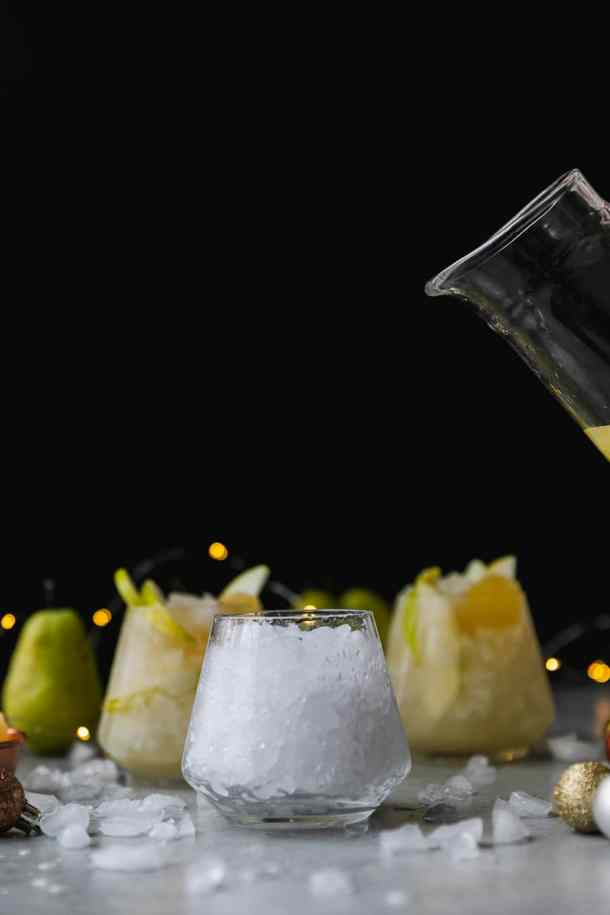 Forward facing shot of a glass pitcher about to pour pear ginger champagne punch into a glass of crushed ice against a black background with twinkle lights