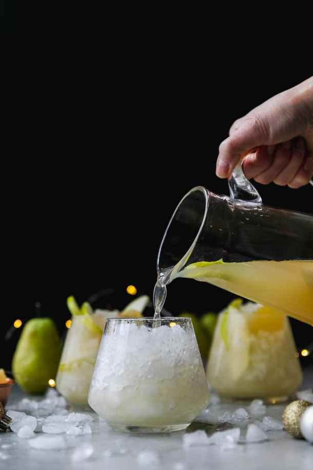 Forward facing shot of a glass pitcher pouring pear ginger champagne punch into a glass with crushed ice with two glasses of punch behind it against a black background