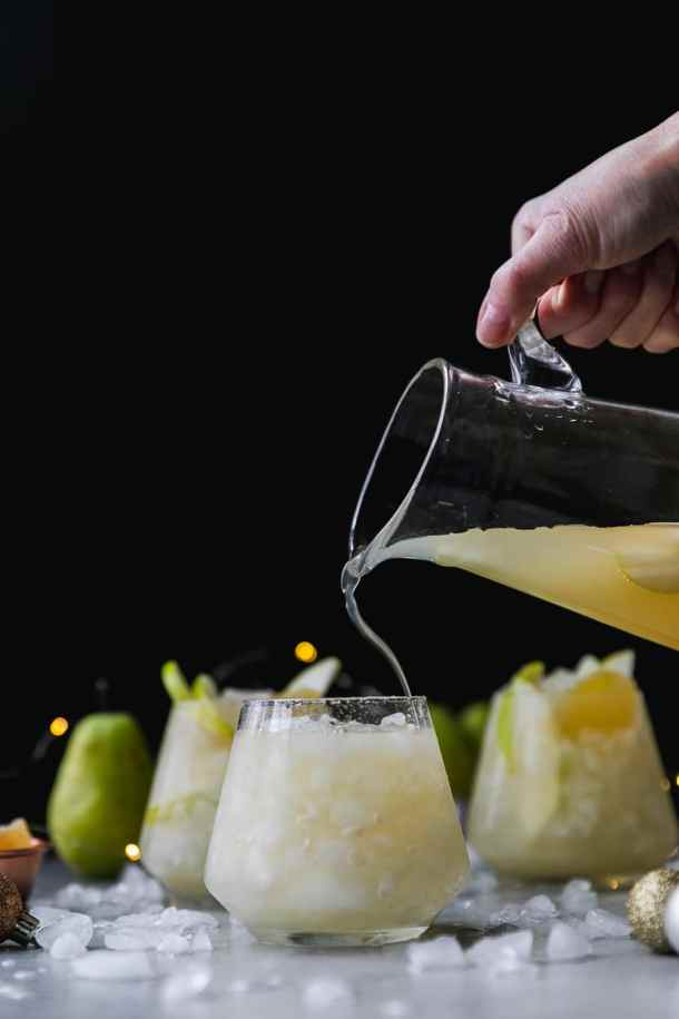 Forward facing shot of a glass pitcher pouring pear ginger champagne punch into a glass with two glasses of punch behind it against a black background