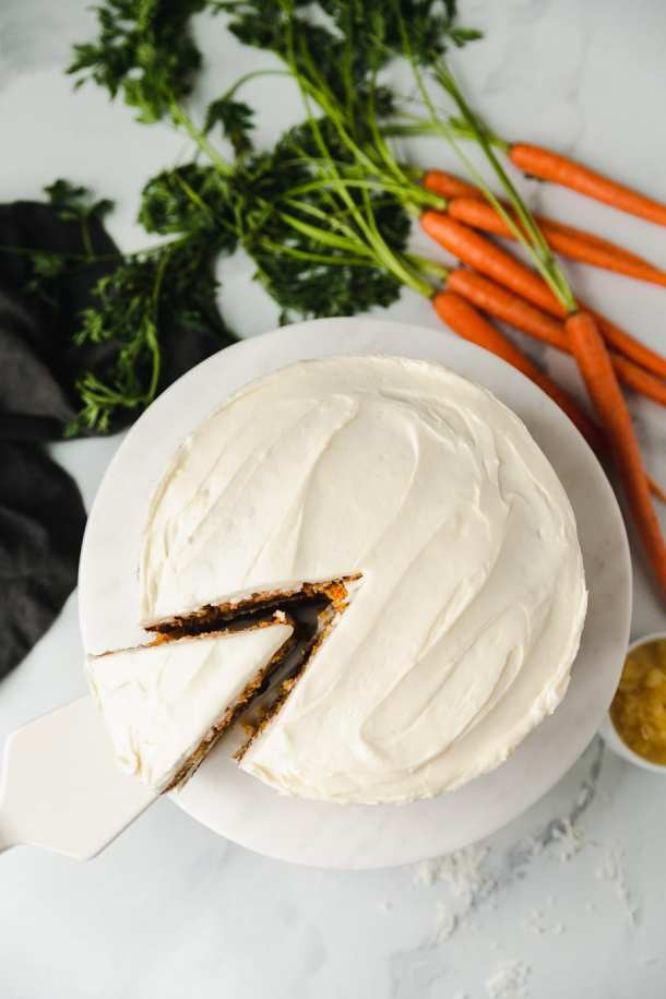 Overhead shot of a carrot cake with a slice being taken out of it and a bunch of carrots with green tops in the background