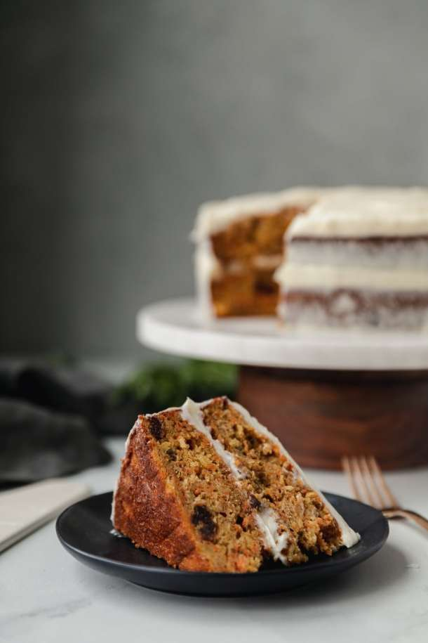 Forward facing shot of a slice of carrot cake on a black plate and a carrot cake on a marble and wooden cake stand behind it