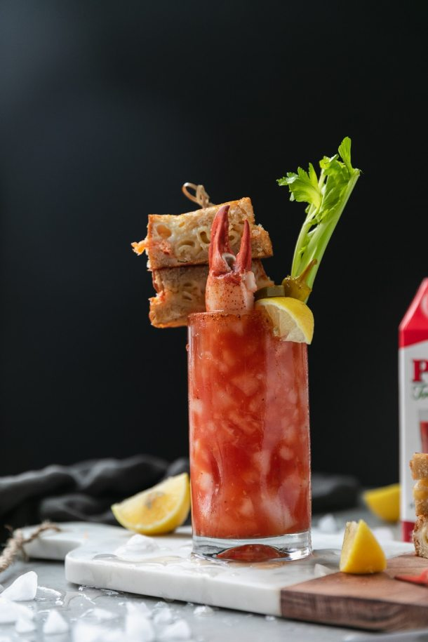 Forward facing shot of a bloody mary garnished with a grilled cheese sandwich on a skewer and a lobster claw sticking out of the drink with a lemon wedge and celery stalk with a grilled cheese sandwich next to it