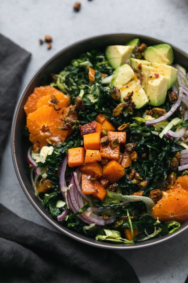 Close up shot of a kale salad with avocado, mandarins, red onion, butternut squash, and candied pistachios with a dark grey napkin next to it