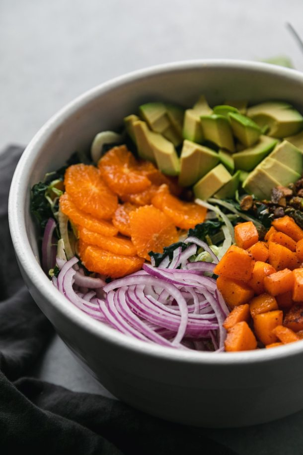Close up shot of a salad bowl filled with kale, brussels, mandarins, red onion, avocado, roasted butternut squash, and candied pistachios