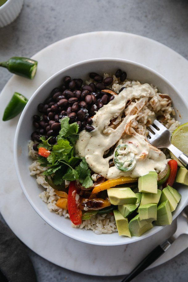 Overhead shot of a fajita burrito bowl topped with cashew queso and a fork taking a bite resting in the bowl