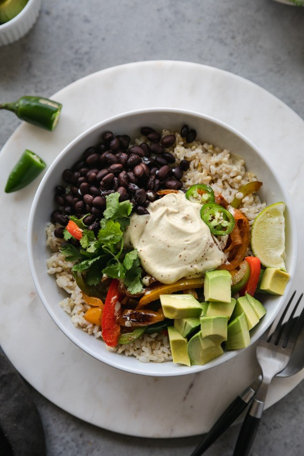 Overhead close up shot of a burrito bowl filled with brown rice, black beans, fajita veggies, avocado, lime, cilantro and cashew queso