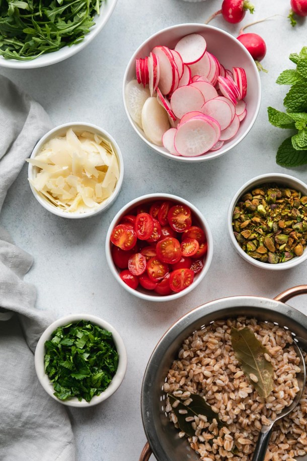 Overhead shot of bowls of arugula, sliced radishes, shaved parmesan, halved grape tomatoes, chopped pistachios, chopped herbs, and a strainer filled with cooked farro and bay leaves