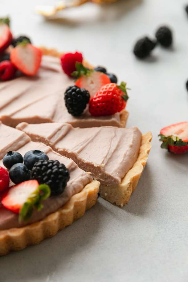 Close up shot of a berry cheesecake tart with a slice about to be taken out