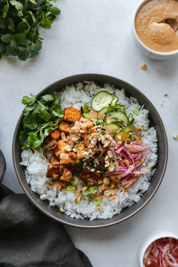 Overhead shot of a rice bowl topped with tofu, pickled vegetables, and cilantro