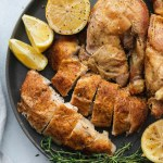 Overhead close up shot of a plate of roasted chicken garnished with thyme sprigs and lemon wedges