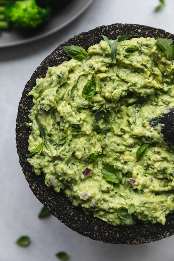 Overhead close up shot of a molcajete filled with green goddess guacamole