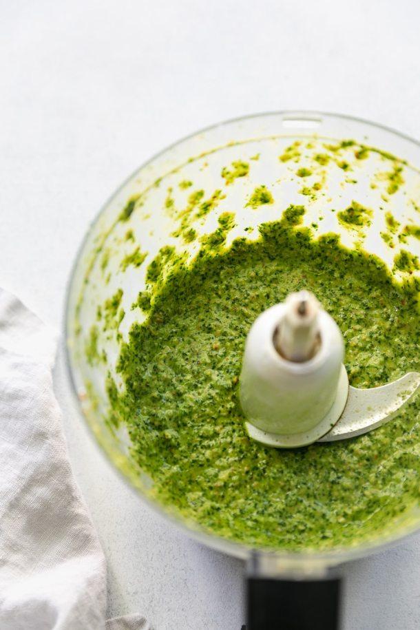Close up shot of a food processor filled with cilantro pepita sauce
