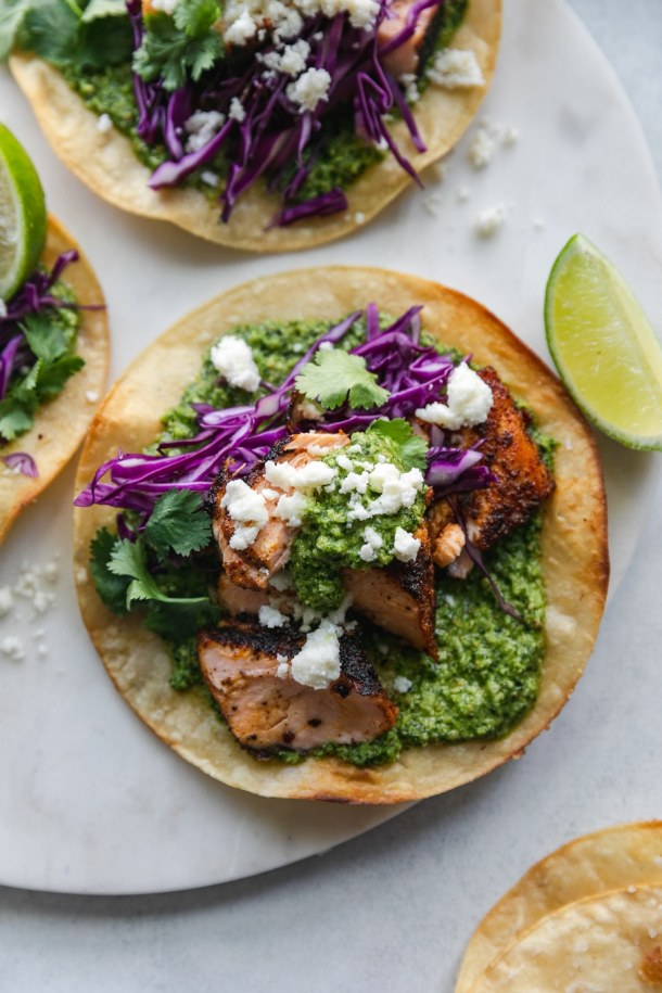 Overhead close up shot of a blackened salmon tostada with green sauce, red cabbage, queso fresco, cilantro, and a lime wedge