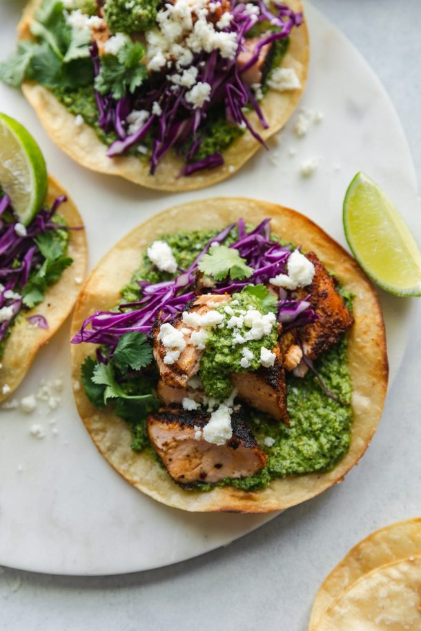 Overhead shot of a blackened salmon tostada with green sauce, red cabbage, queso fresco, cilantro, and a lime wedge