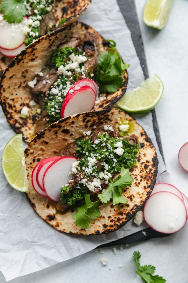 Overhead shot of charred tortillas filled with grilled carne asada, chimichurri sauce, cilantro, sliced radishes, cotija cheese, and lime wedges