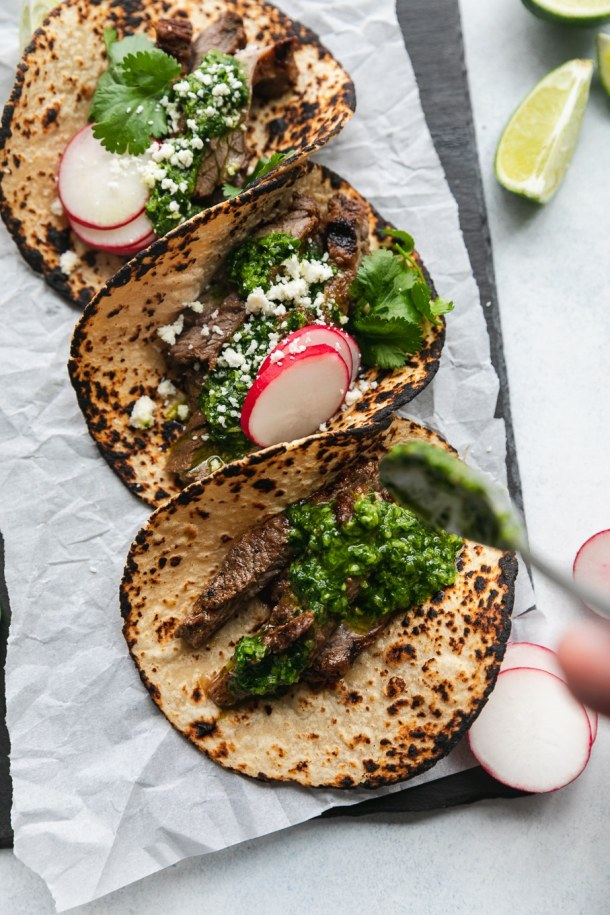 Overhead shot of charred tortillas being drizzled with green chimichurri sauce