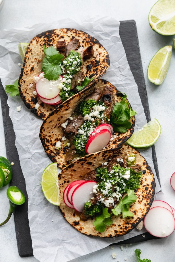 Overhead shot of 3 charred tortillas filled with grilled carne asada, chimichurri sauce, cilantro, sliced radishes, cotija cheese, and lime wedges