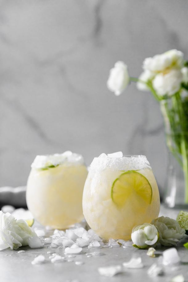 Forward facing shot of two elderflower margaritas with a vase of white flowers in the background