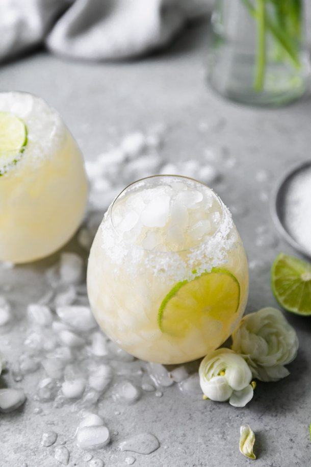 Close up shot of an elderflower margarita with small white flowers, crushed ice, and a lime wedge next to it