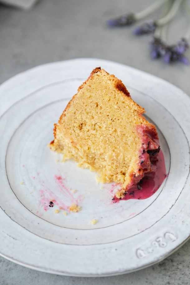 Close up shot of a piece of lemon pound cake with blueberry glaze with a few bites taken out