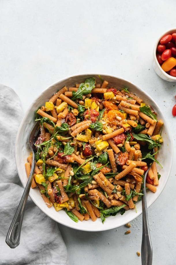 Overhead shot of a bowl of pasta filled with roasted tomatoes, summer squash, arugula, and parmesan cheese with two large silver utensils in the bowl