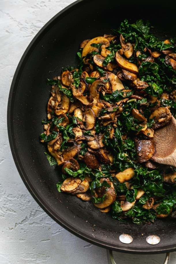 Overhead shot of a skillet filled with sautéed mushrooms and kale