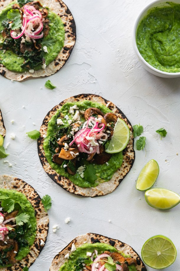 Overhead shot of mushroom kale tacos with avocado cilantro sauce and pickled red onions