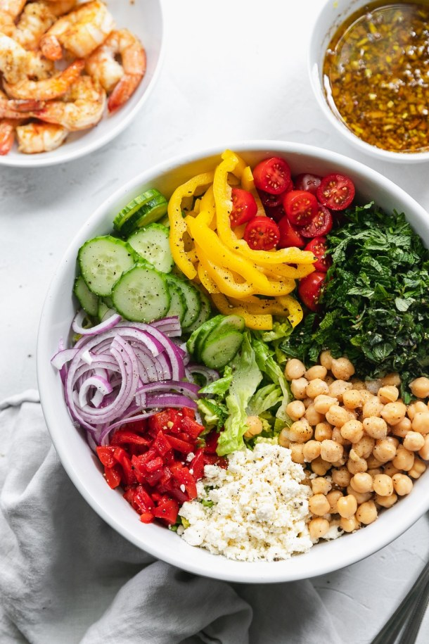 Overhead shot of a mixing bowl filled with mediterranean chopped salad ingredients