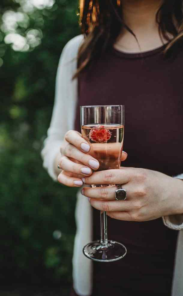 Shot of a woman holding a glass of champagne with a raspberry floating in it