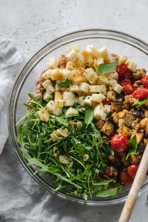 Overhead shot of a bowl filled with a pile of arugula, a pile of cubed smoked mozzarella, and roasted tomatoes and eggplant