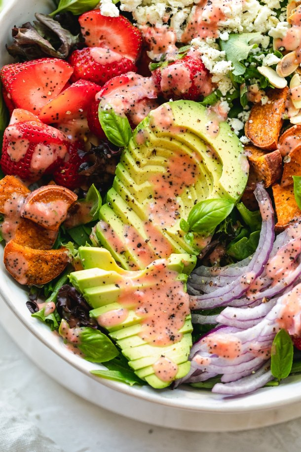 Overhead close up shot of a salad with sliced avocado, strawberries, and roasted strawberry poppyseed vinaigrette