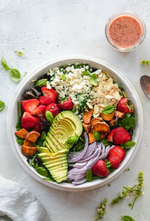 Overhead shot of a colorful salad with avocado, strawberries, and red onion
