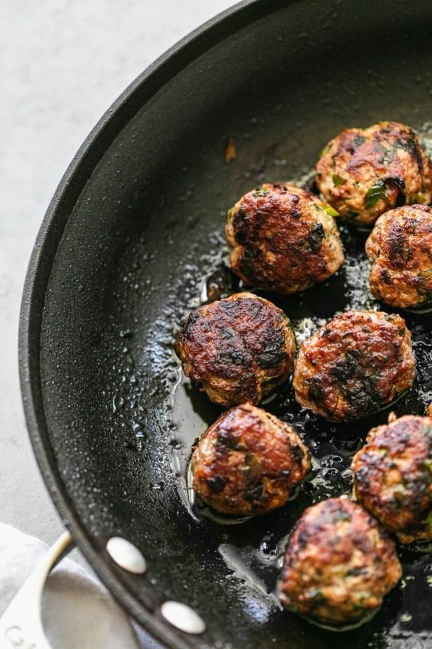 Close up shot of pork meatballs in a skillet