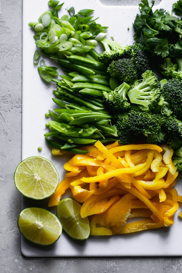 Overhead shot of a cutting board with vegetables and limes