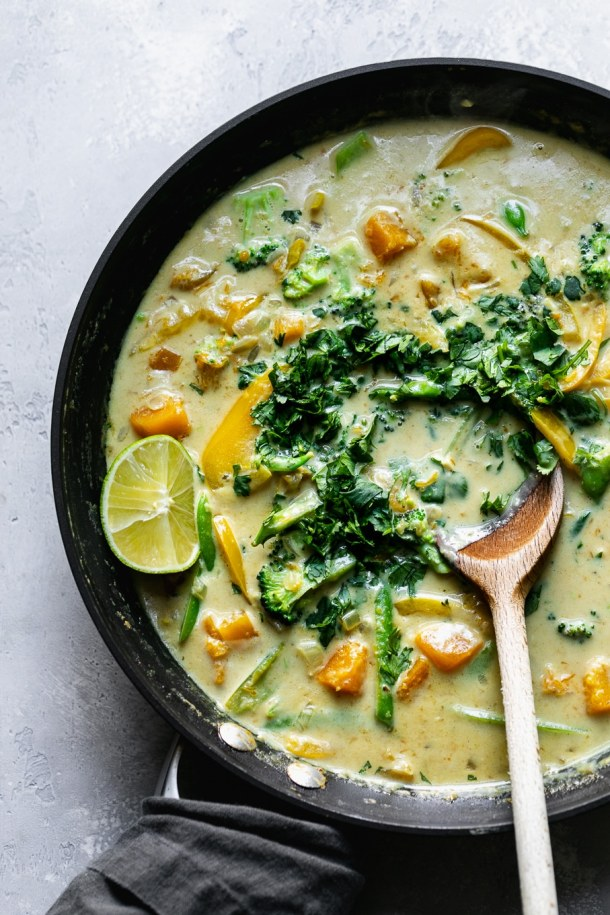Shot of a skillet filled with vegetable green curry and a wooden spoon
