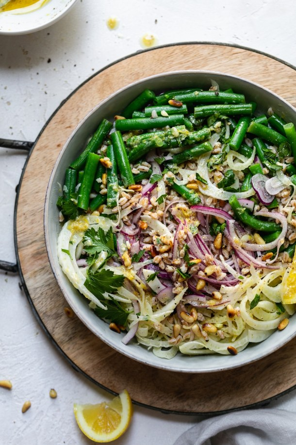 Overhead shot of a colorful green bean salad on a wooden board