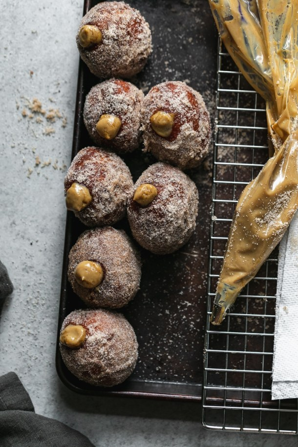 Overhead shot of dirty chai cream filled doughnuts on a baking sheet with a pastry bag