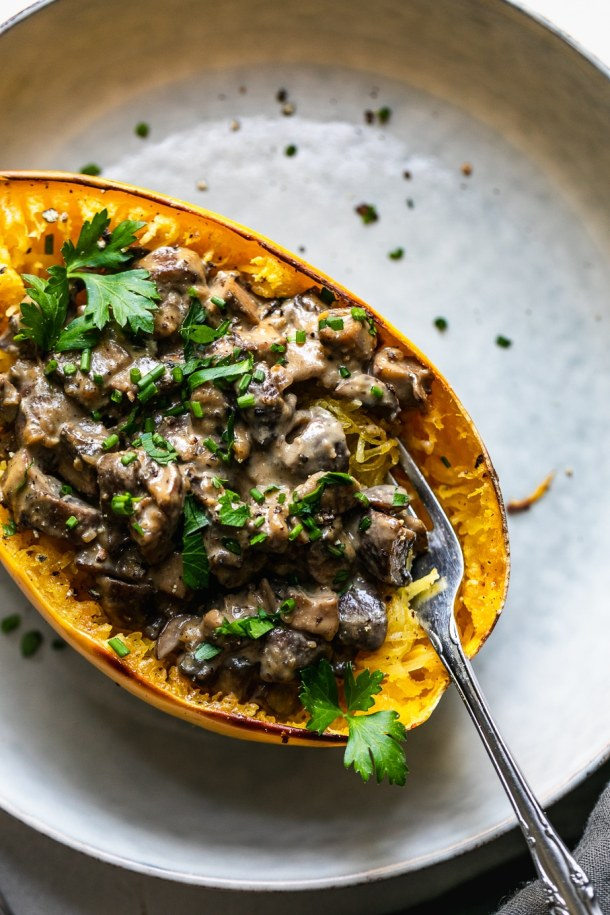 Overhead close up shot of a creamy mushroom spaghetti squash boat with a fork digging in